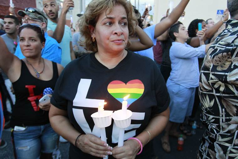 Brenda Chirino, one of hundreds that gathered at the Metro Wellness Center in Ybor City, attends a candlelight vigil to honor the victims of the nightclub shooting in Orlando, Fla., Sunday, June 12, 2016. Tampa Police momentarily shut down a portion of 7th avenue to accommodate the large crowd. (Luis Santana/Tampa Bay Times via AP)